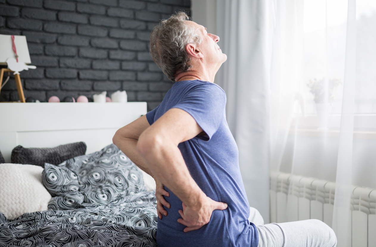 man with chronic back pain getting out of bed